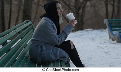 young girl drinking coffee in a winter park sitting on the bench