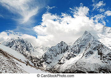 Dombay - Mountain peaks in sun windy day Caucasus Mountains,...