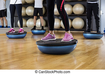 Low Section Of Friends Standing On Bosu Ball In Gym - Low...