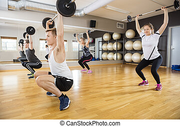 Determined Men And Women Lifting Dumbbells On Hardwood Floor...