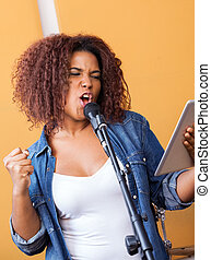 Passionate Singer Holding Tablet Computer While Performing