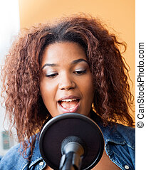 Young Woman Singing In Recording Studio - Closeup of young...