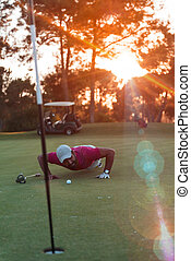 golf player blowing ball in hole with sunset in background -...