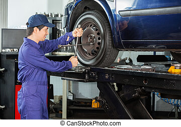 Mechanic Fixing Car Tire At Repair Shop - Side view of male...