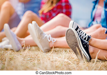 Legs of teenagers, canvas shoes, summer music festival