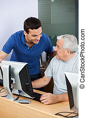 Teacher Looking At Senior Man Using Computer Classroom