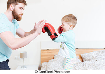 Little son in boxing gloves playing with his father - Cute...
