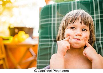 Cute little girl outside in garden holding her cheeks, sunny...