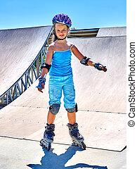 Girl riding on roller skates in skatepark. Roller skates is...