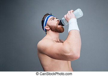 Shirtless bearded sportsman drinking water from plastic...