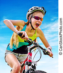 Bikes cycling girl wearing helmet rides bicycle aganist blue...