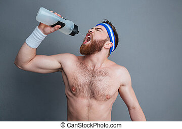 Shirtless bearded young man athlete standing and drinking...