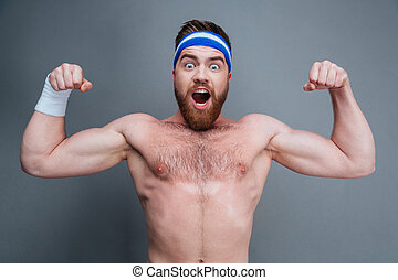 Happy amazed young sportsman standing and showing biceps