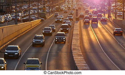 cars go on the road in the sunset light