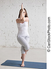 Side view portrait of woman doing Eagle Pose Pose -...