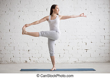 Beautiful woman doing Revolved Extended Hand to Big Toe pose...