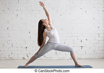 Side view portrait of happy woman doing Reverse Warrior Pose...