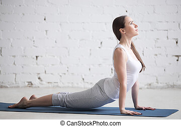 Attractive young woman doing upward facing dog pose in white...