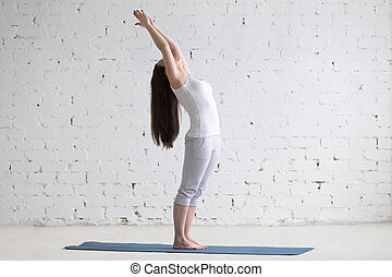 Beautiful sporty young woman doing standing backbend pose in...