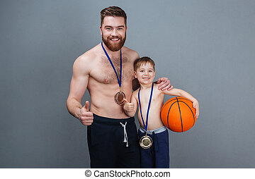 Cheerful man and son with golden medals holding basketball...