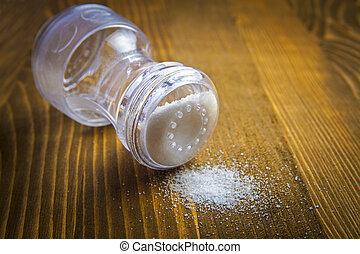 Salt shaker and heap of salt