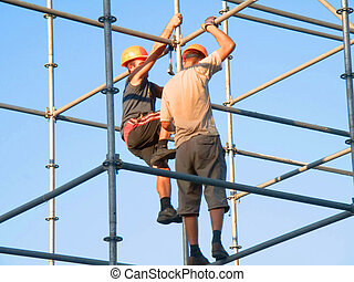 Construction Worker - Two ironworkers atop the skeleton of a...