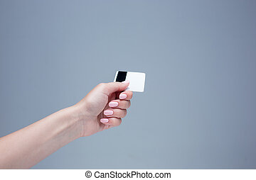 The card in a female hand is on a gray background