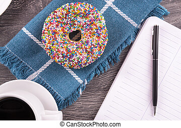 Break time - Donut and coffee cup on wooden table, top view.