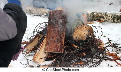 Kindling of fire from sticks and logs Difficult process of...