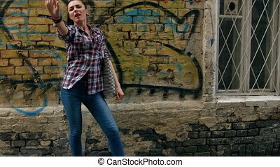Young woman  in checkered shirt and blue jeans dancing laughing against wall with graffiti