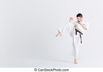 Male fighter in kimono posnig isolated on a white background