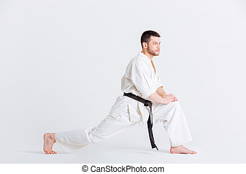 Man in kimono warming up isolated on a white background