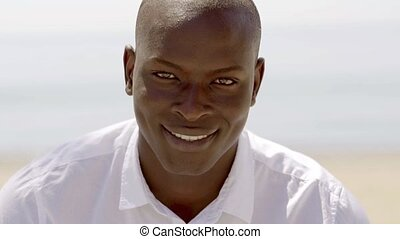 Close up of smiling black male model in white dress shirt...