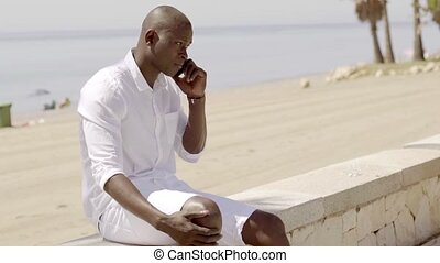 Man arguing on phone while seated on stone wall by beach on...