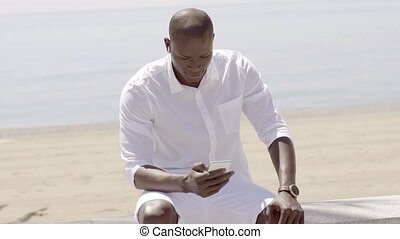 Man listening to music on cell phone while seated near beach...