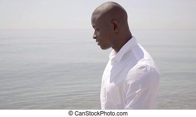 Thoughtful African man walking along the sea - Thoughtful...