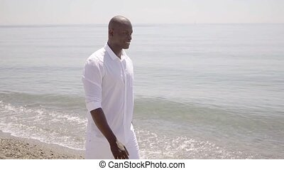 Healthy trendy young African man at the beach striding along...