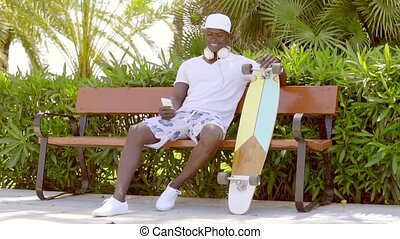 Handsome sporty African man with a skateboard relaxing on a...