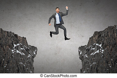 happy smiling businessman jumping between rocks - business,...
