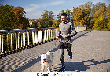happy man with labrador dog running outdoors - fitness,...