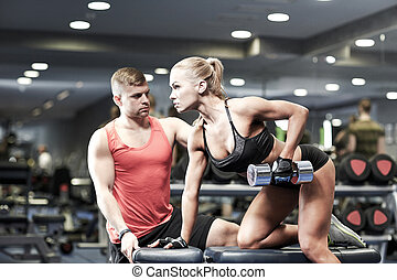 young couple with dumbbell flexing muscles in gym - fitness,...