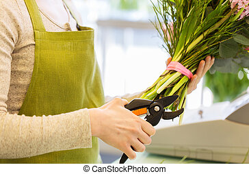 close up of florist woman with flowers and pruner - people,...
