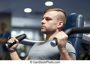 man exercising and flexing muscles on gym machine - sport,...
