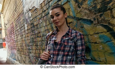 Portrait of smiling beautiful fashion woman in checkered shirt against wall with abstract graffiti