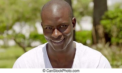 Smiling handsome bald black man in the park while wearing...