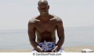 Seated muscular black man near beach and ocean wearing only...