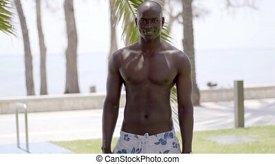 Muscular black man bares his chest near grass and palm trees...