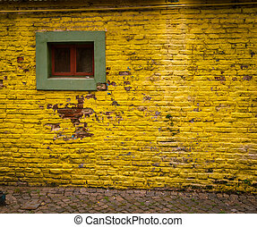 yellow brick wall - Yellow brick wall with a green window