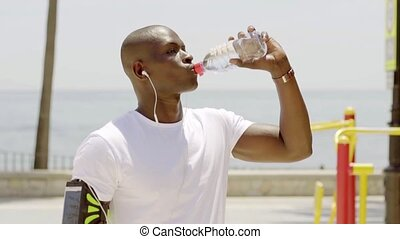 Black male athlete finishing his sports beverage while...