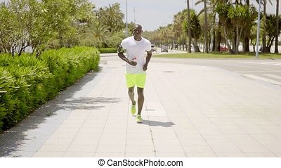 Man wearing bright yellow shorts and music device on arm...